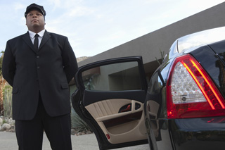 Chauffeur waiting outside armoured limousine